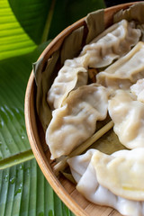 steamed pot stickers dumplings in bamboo basket on banana leaves