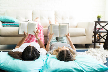 Relaxed Friends Reading Interesting Stories At Slumber Party