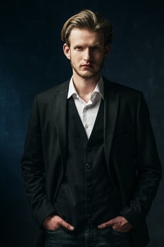 Studio portrait of young handsome confident man wearing white shirt, black jacket, vest, posing on dark background