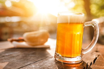 Foto auf Gartenposter Bier / Apfelwein cold glass mug of beer with foam with bratwurst hotdog with sun beams