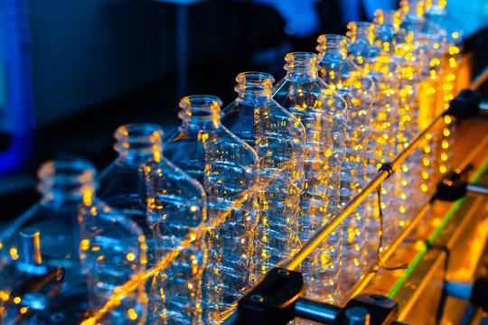 Bottle. Industrial production of plastic pet bottles. Factory line for manufacturing polyethylene bottles. Transparent food packaging.