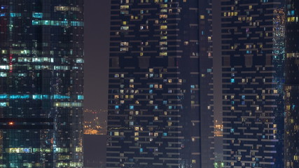 Window of the multi-storey skyscrapers of glass and steel office lighting and people within timelapse