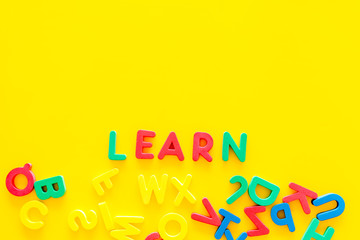 Children learn read concept. Word learn written by plastic letters on yellow background top view copy space
