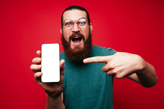 Amazed bearded man pointing at white screen on smartphone.