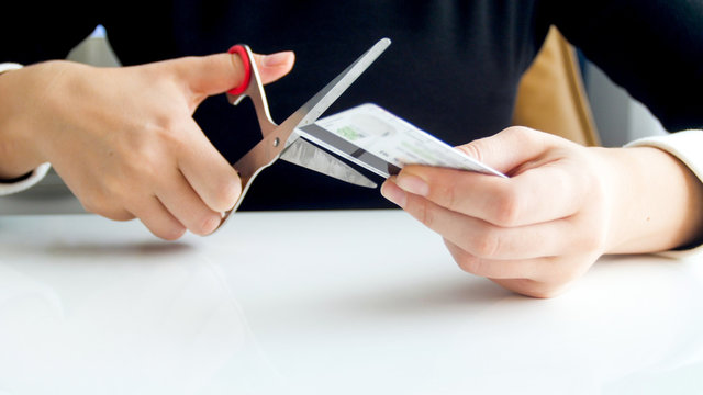 Closeup photo of young woman in suit cutting expired credit card with scissors