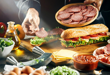 Chef preparing tasty fresh baguette sandwiches