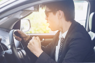 Driving men is strain in car on the road.