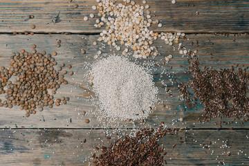 Gluten free grains ( brown rice, peas, flax seeds, lentils, white quinoa) on wooden background.