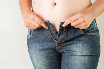 Overweight fat woman wearing jeans. Weight loss stomach closeup. Skinny jeans on a healthy slim fit body. Diet concept.