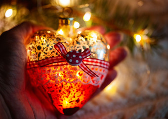 Female hand holds a glass heart, a Christmas toy - a garland in the hands on the background of a warm knitted sweater. Evening time. In red tones