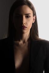 Ritratto di viso di donna carina e femminile splendida con labbra rosse e rossetto e trucco leggero in controluce con pelle abbronzata e femminilità  sguardo intenso primo piano in studio fotografico
