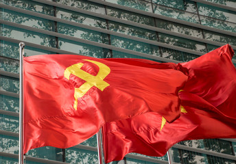 The red flag with communist symbols of a sickle and a hammer flying by building.The Red flag with a five-pointed star flutters on the pole.