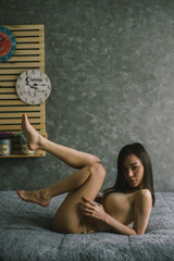 sexy asian woman in biege lingerie on the bed