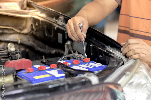 A Man Are Removing The Battery Terminals From Car To Work On Electrical System Using Wrench