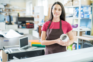 Pretty young woman in apron holding paper roll and smiling at camera working in typography office