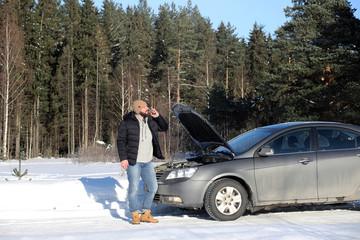 Man stands outdoor near broken car