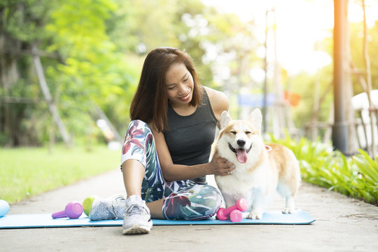 A healthy woman playing with a corgi puppy while exercising on yoga mat surrounding with gym tools such as kettlebell and dumbbell, outdoor training with dog