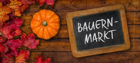 Herbstlaub mit Kürbis auf einem Holzbrett mit Tafel - Bauernmarkt