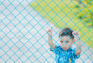 The boy stands behind the fence.