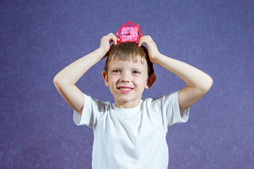 A little boy in a white T-shirt on a purple background holds a pink clock over his head and laughs
