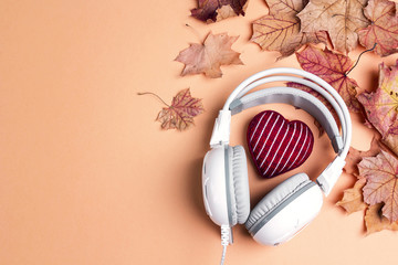 White headphones with red knitted heart, autumn maple leaves and copy space. Top view, flat lay.