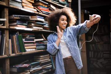 African american pretty woman charful student making selfie photo on front camera of smartphone for sharing in networks using wi-fi and 5g internet preparing for exam in library