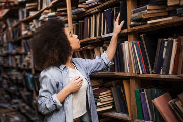Young female african american librarian making order on bookshelves in college, dark skinned woman student picking literature for education checking information in books store, hipster girl get novels
