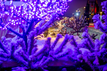Christmas background with snow-covered fir trees and illuminations