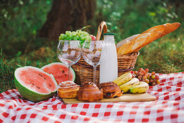 Aluminium Prints Picnic Healthy food for picnic outside. Closeup view of fresh buns, bread, yogurt, bananas, watermelon, green grape and red apples. Horizontal color image.