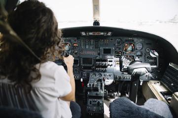 Brunette woman navigating plane