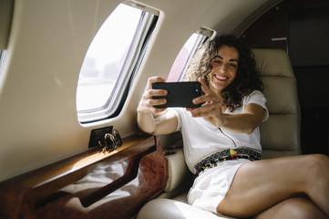 Woman making selfie in airplane