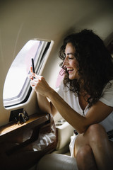 Woman taking pictures through airplane window