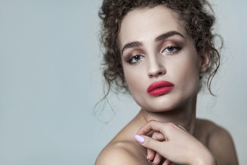 Beauty portrait of young beautiful fashion model with collected dark curly hair, nude makeup and red lips looking at camera with serious face. indoor studio shot. isolated on gray background.