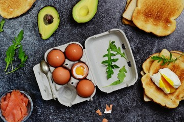 Poached egg toast isolated. Breakfast tost with soft boiled egg, avocado and salmon on the black background