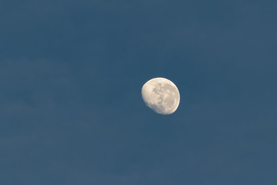 Almost full yellow moon in blue sky