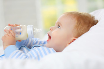 Charming blue-eyed baby 7 month old lies in bed and drinks milk from a bottle