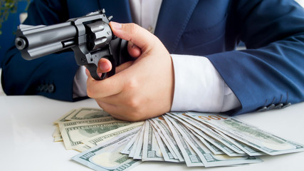 Closeup image of businessman with stack of money aiming with revolver