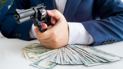 Closeup image of businessman in suit protecting his money and aiming with handgun