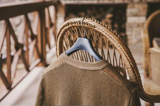 Jacket woolen hanging on wicker chair