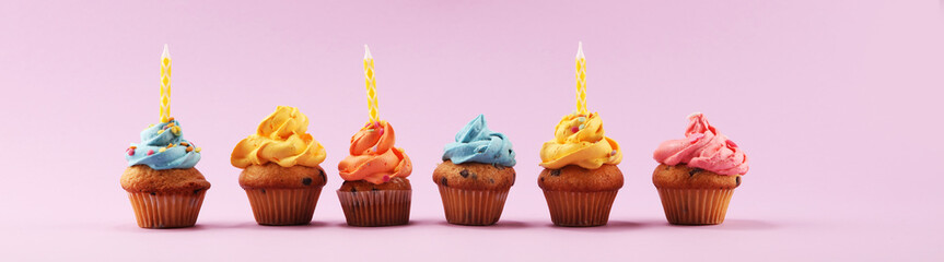 Tasty cupcakes on pinke background. Birthday cupcake in rainbow colors.