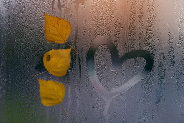 Three Yellow autumn leaves with heart on window after rain. Concept autumn mood.