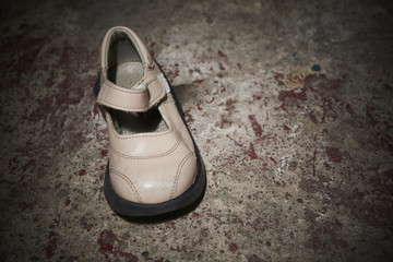 Abandoned baby shoe lying on old concrete floor. Lost children's shoes.