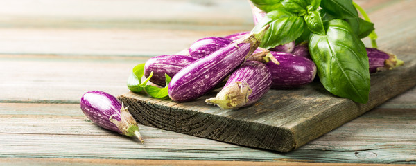 Heap of small eggplant or aubergine vegetable with basil leaves on old wooden background. Healthy food concept with copy space. Banner.