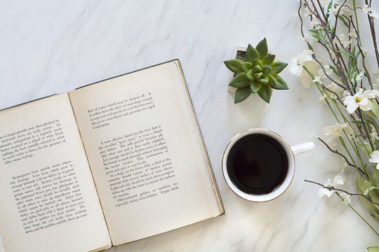 flatly of book and coffee on table for morning relaxing time