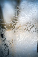 Frosty patterns on the frozen window are macro. Winter background