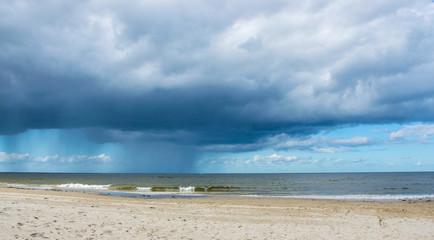 Dark rain clouds above the Baltic sea. Raining.