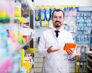 Positive male pharmacist offering right drug