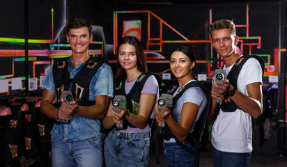 Smiling young people with laser guns having fun together in labyrinth