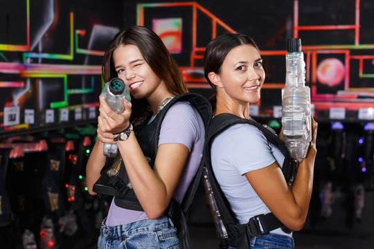 Girl took aim and holding guns during laser tag game in dark labyrinth indoor