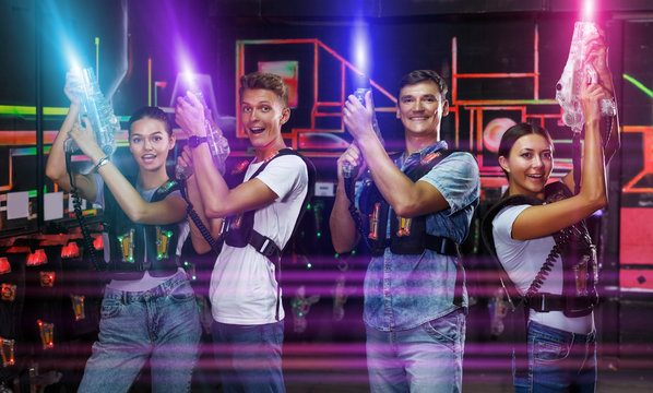 people with laser guns having fun together in dark labyrinth